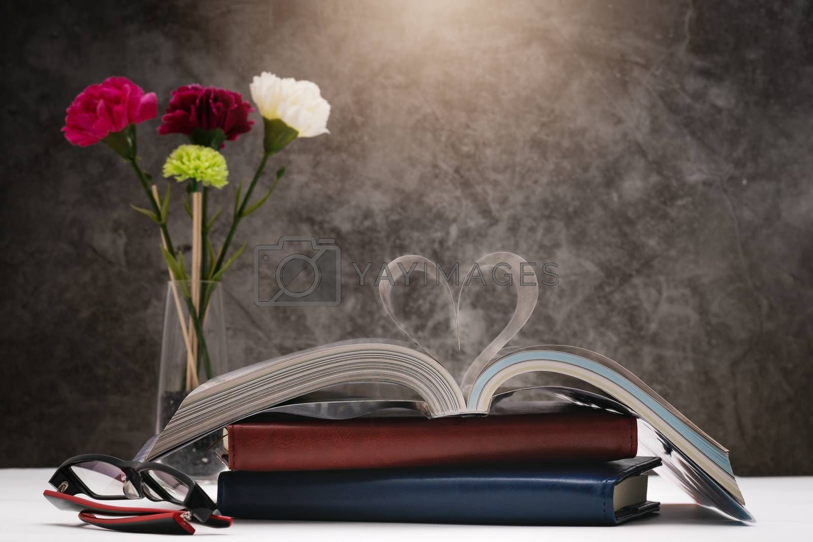 Love story book with open page of literature in heart shape and glasses