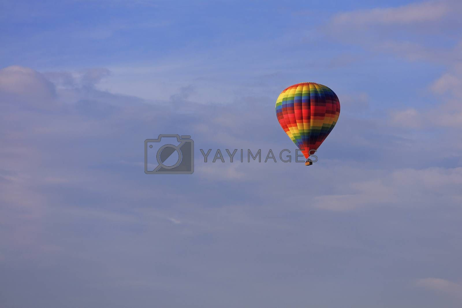 A motley multicolored beautiful balloon raises the tourist's basket to the blue sky under the sun rays among the clouds.