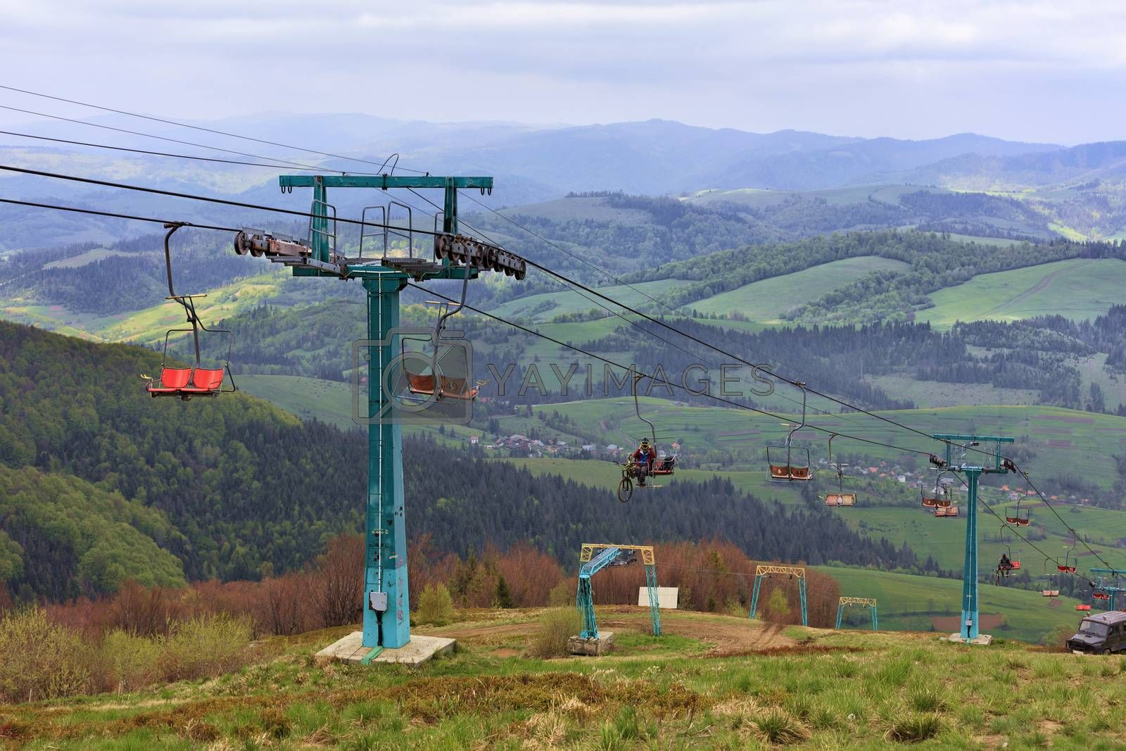 The ski-lift carries tourists and athletes up and down the mountains against the backdrop of the summer mountain scenery in the Carpathians