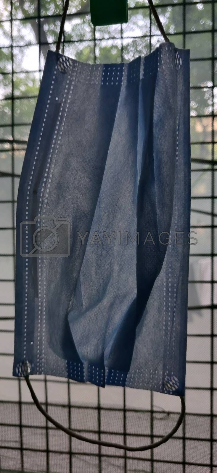 Close up of one surgical mask hanging by clothes pin near a grilled window during lock down in India
