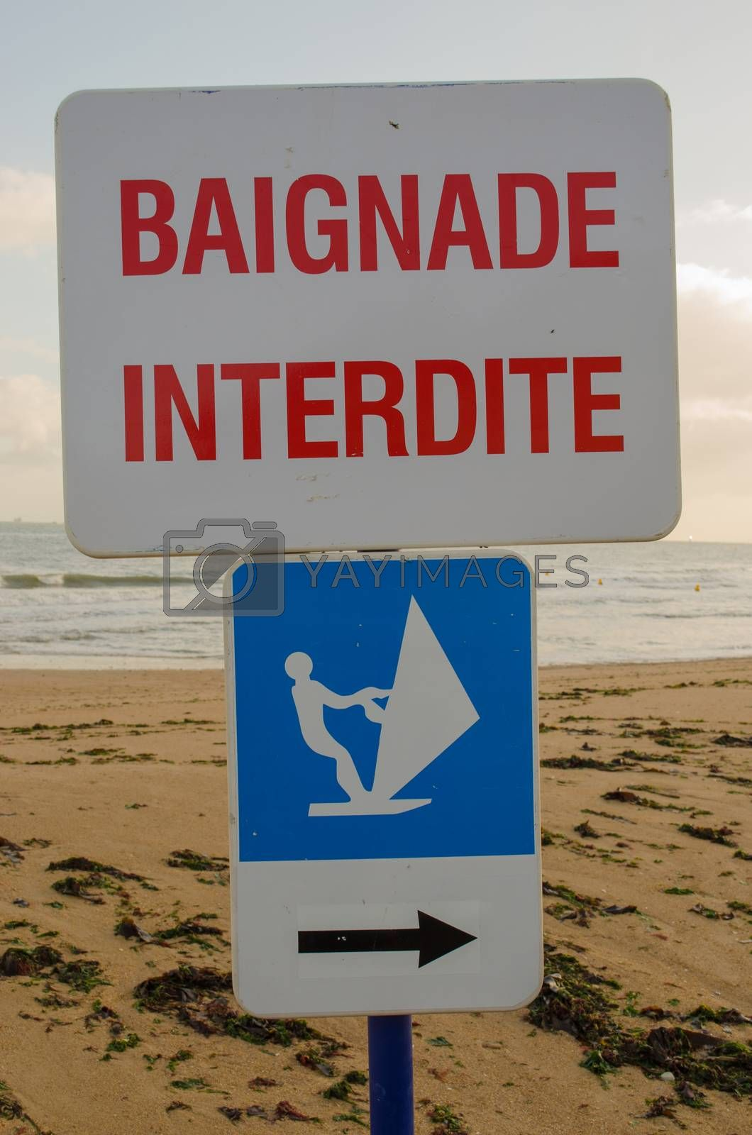 2 French signs. One prohibits bathing in the sea and the other allows wind surfing.
