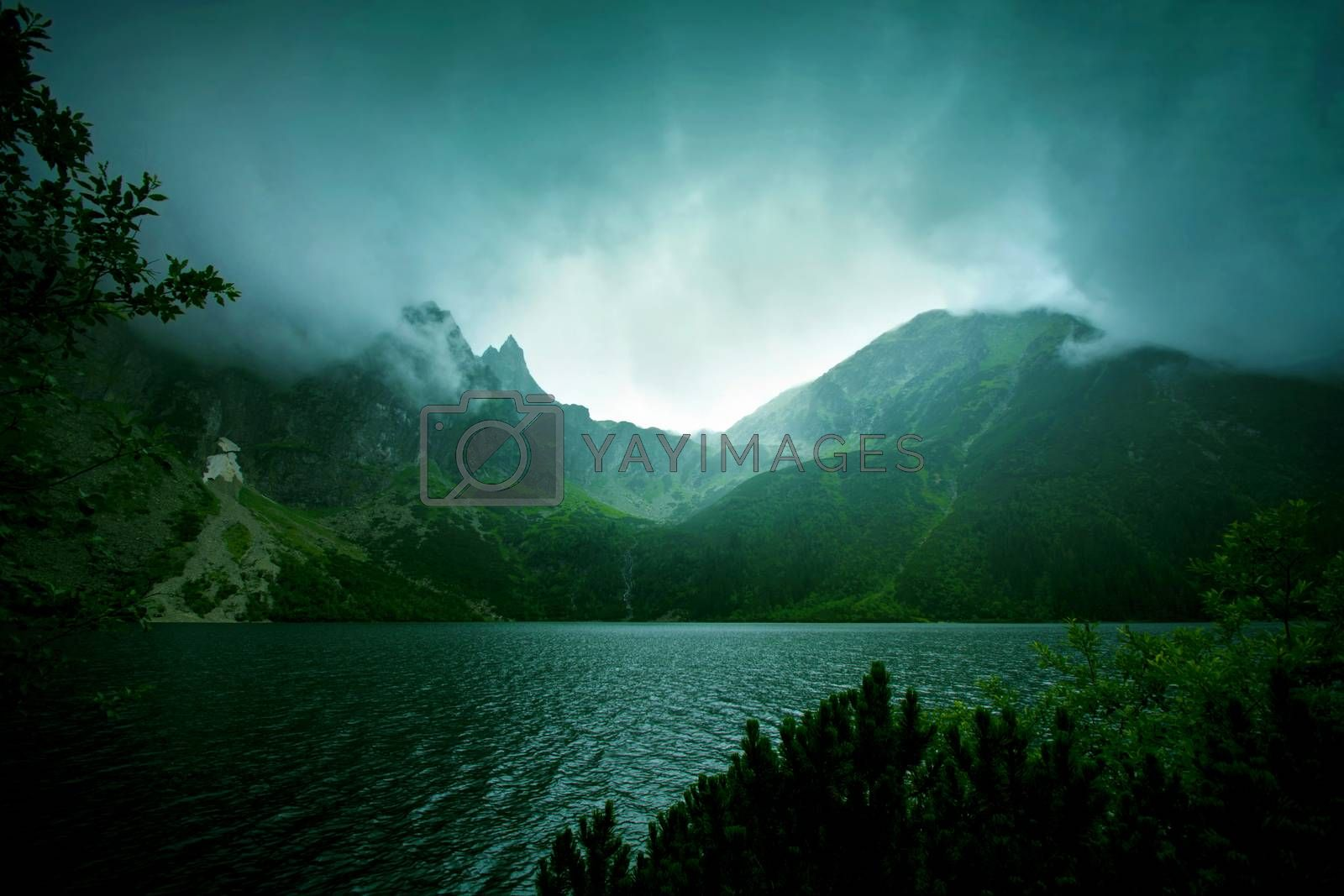 Fog and dark clouds in mountains. Lake in mountains.