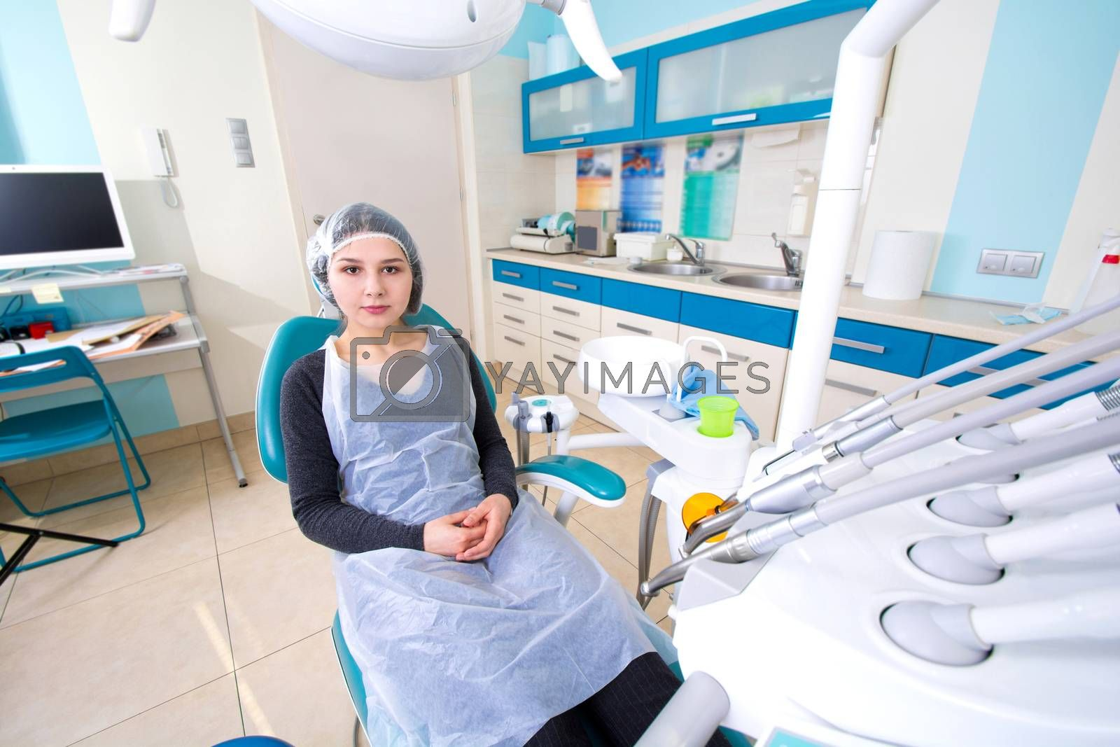 Female patient waiting for dental treatment in a dental chair. Dental Hygiene and Health conceptual image.