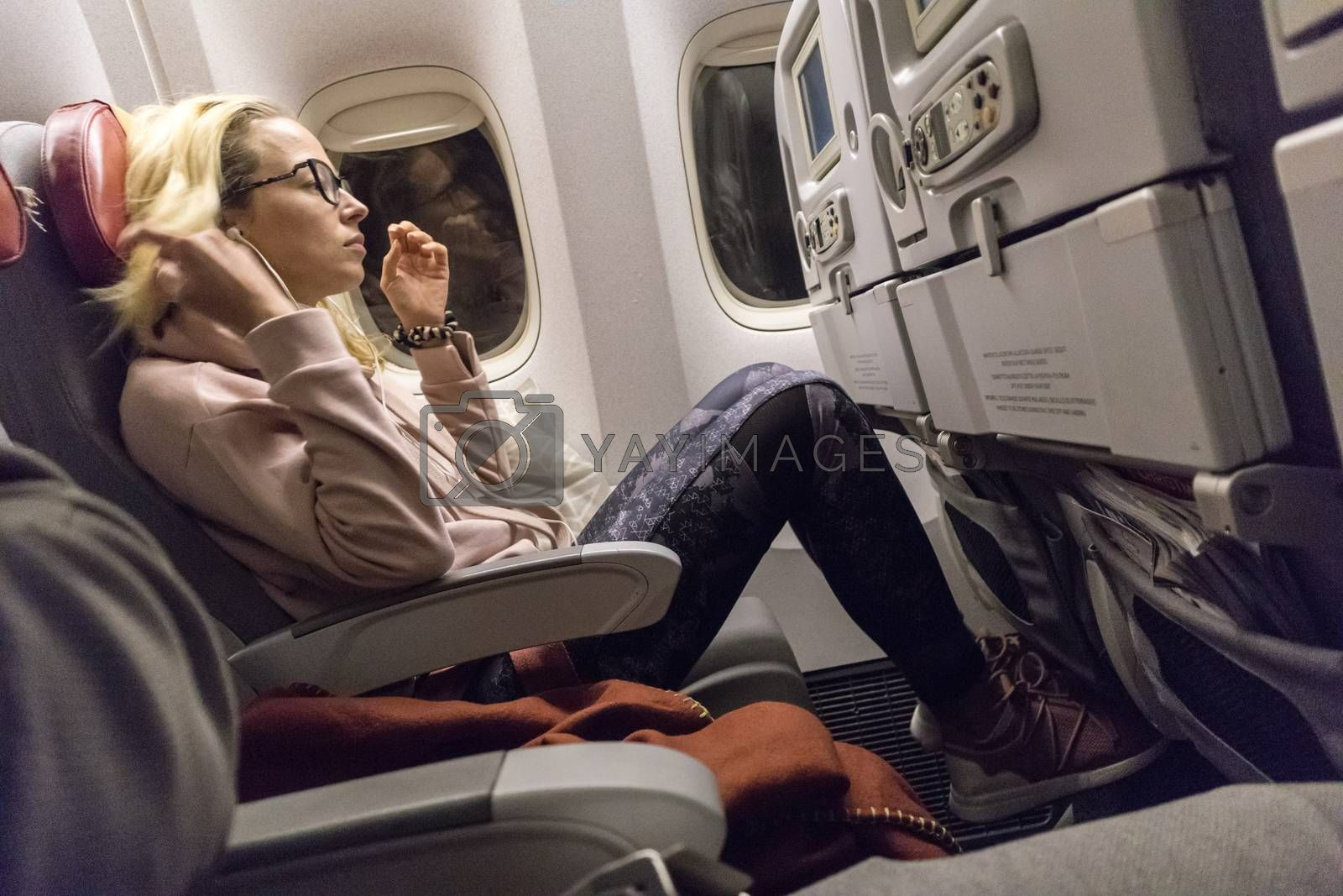 Sporty casual young blonde caucasian lady watching movie while traveling by airplane by the window. Commercial transportation by planes.
