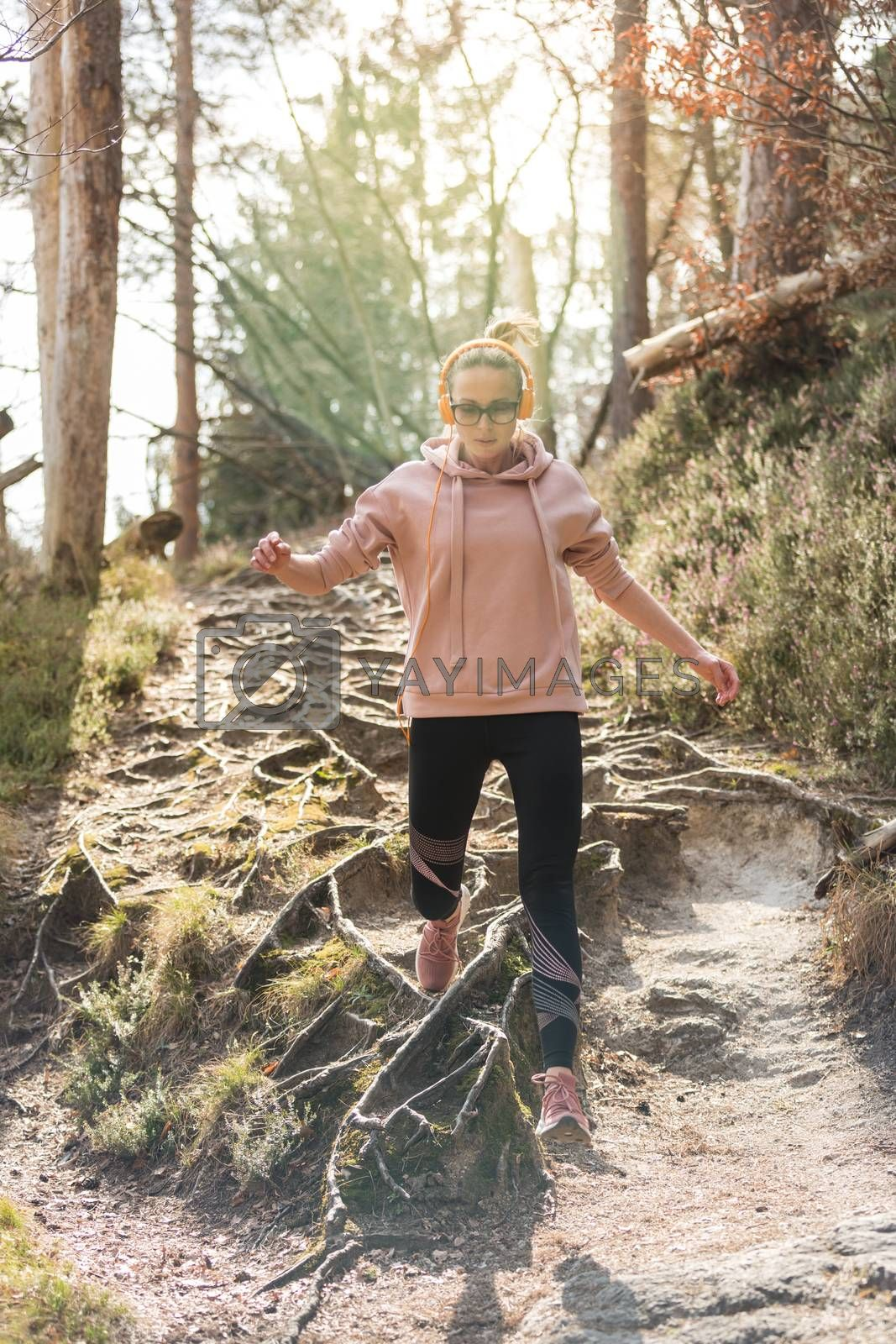 Active sporty woman running in autumn fall forest jumping over the roots on the path. Healthy lifestyle image of young active caucasian woman jogging outside in nature.