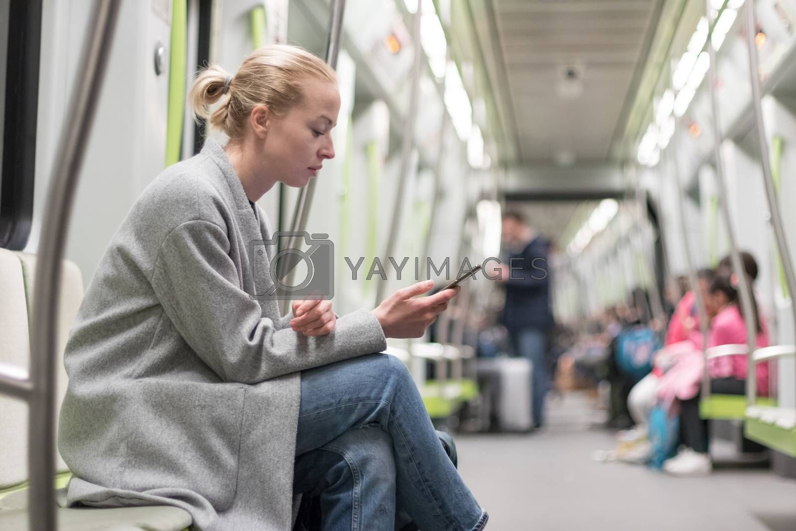 Portrait of lovely girl typing message on mobile phone in almost empty public subway train. Staying at home and social distancing recomented due to corona virus pandemic outbreak.
