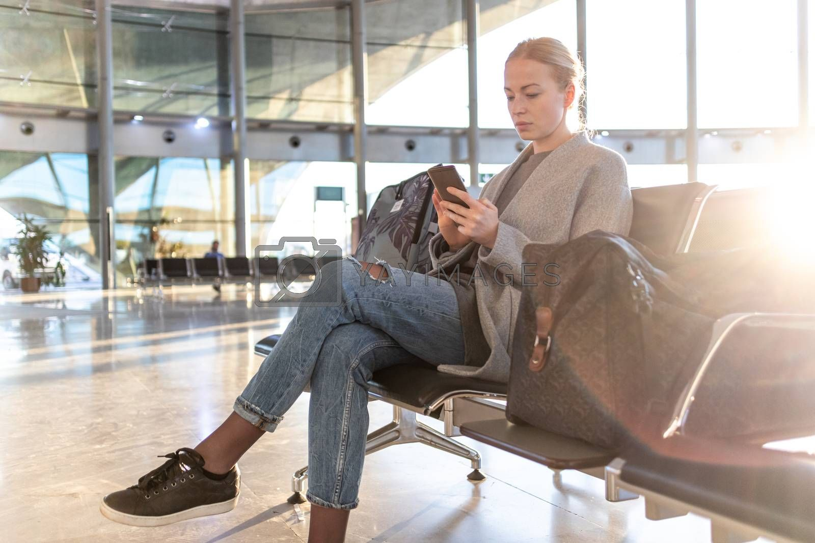 Casual blond young woman talking on cell phone while waiting to board a plane at airport departure gates. Empty airport terminal due to corona virus pandemic.