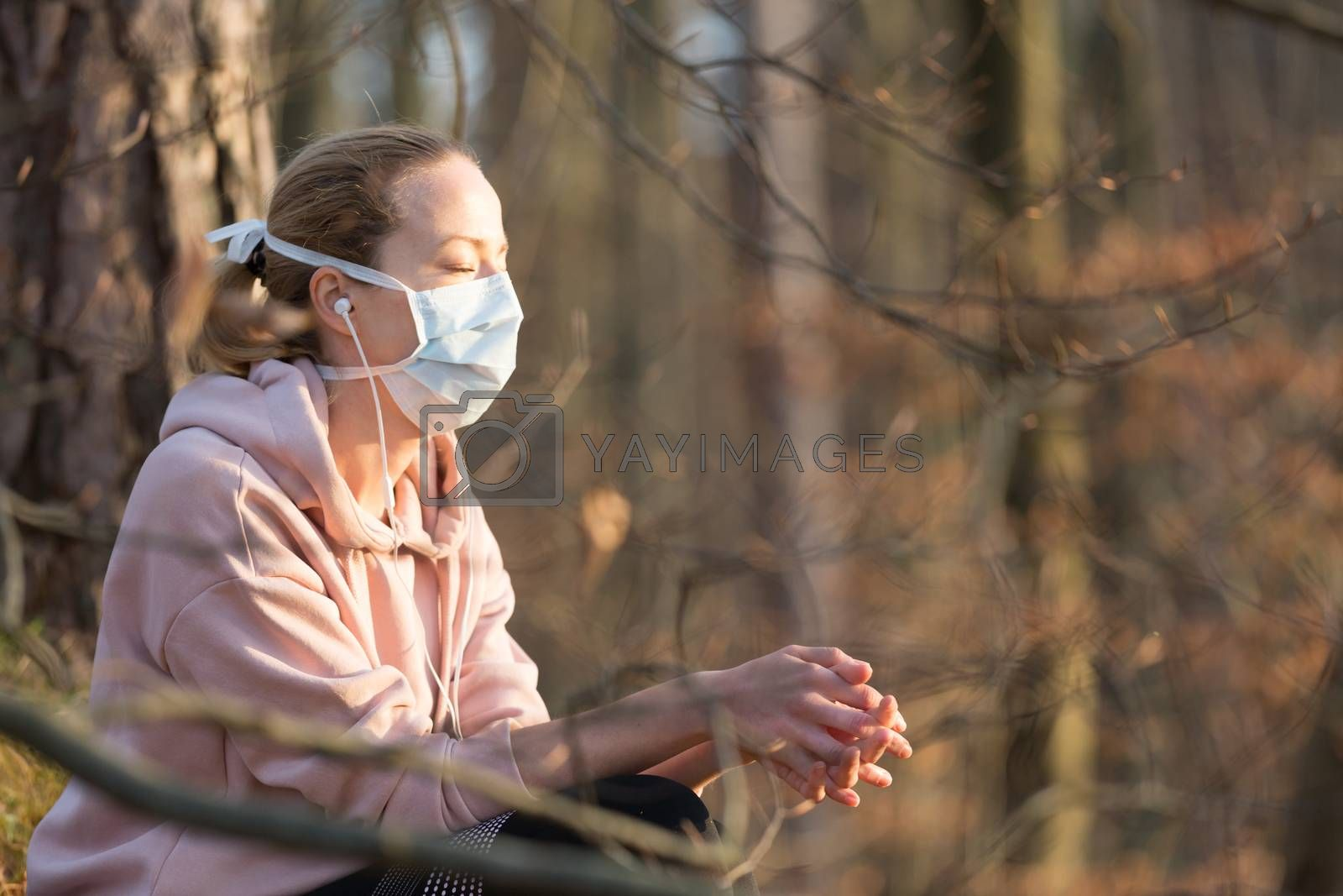 Portrait of caucasian sporty woman wearing medical protection face mask while relaxing in nature and listening to music. Corona virus, or Covid-19, is spreading all over the world.