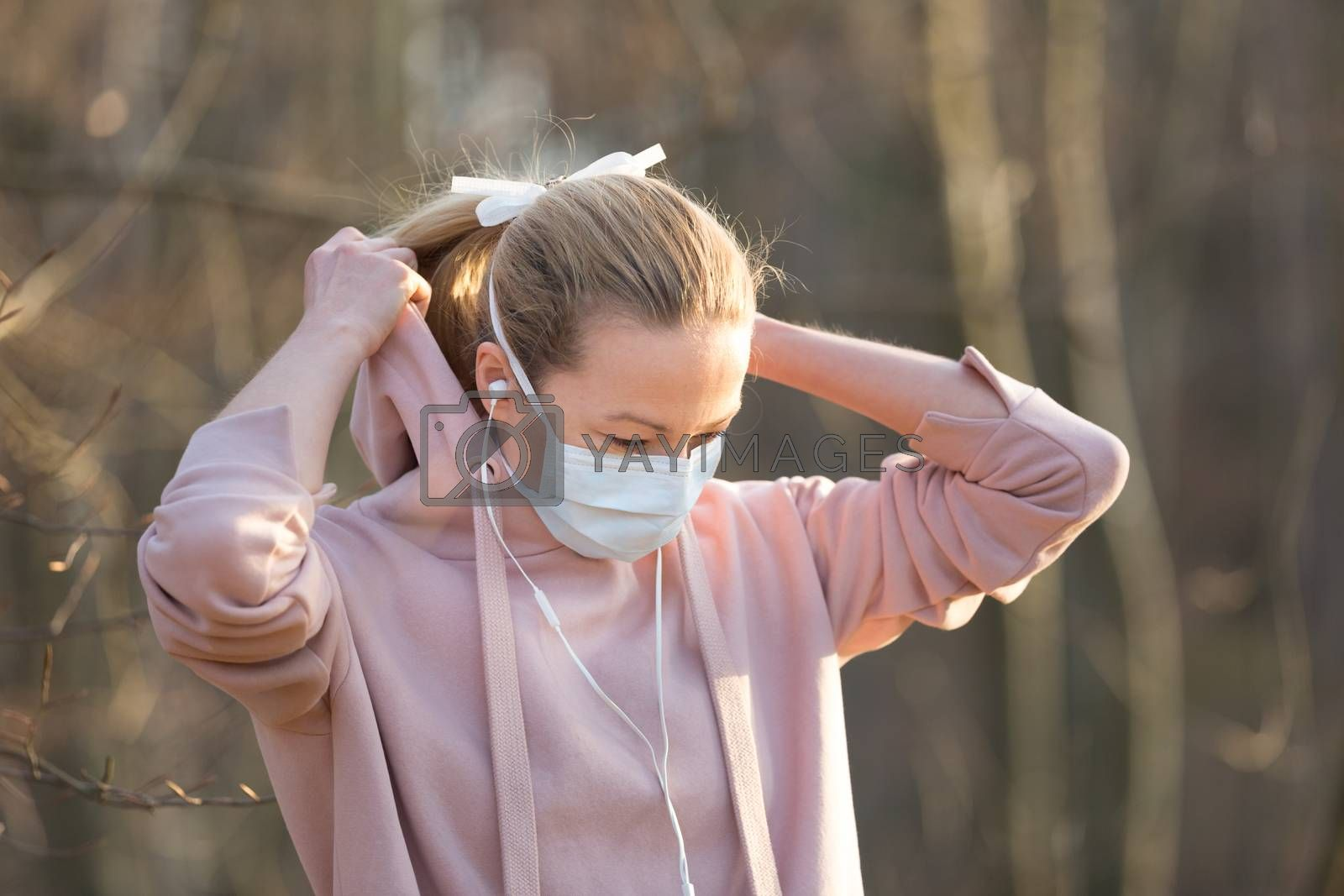 Portrait of caucasian sporty woman wearing medical protection face mask while walking in park, relaxing and listening to music. Corona virus, or Covid-19, is spreading all over the world.