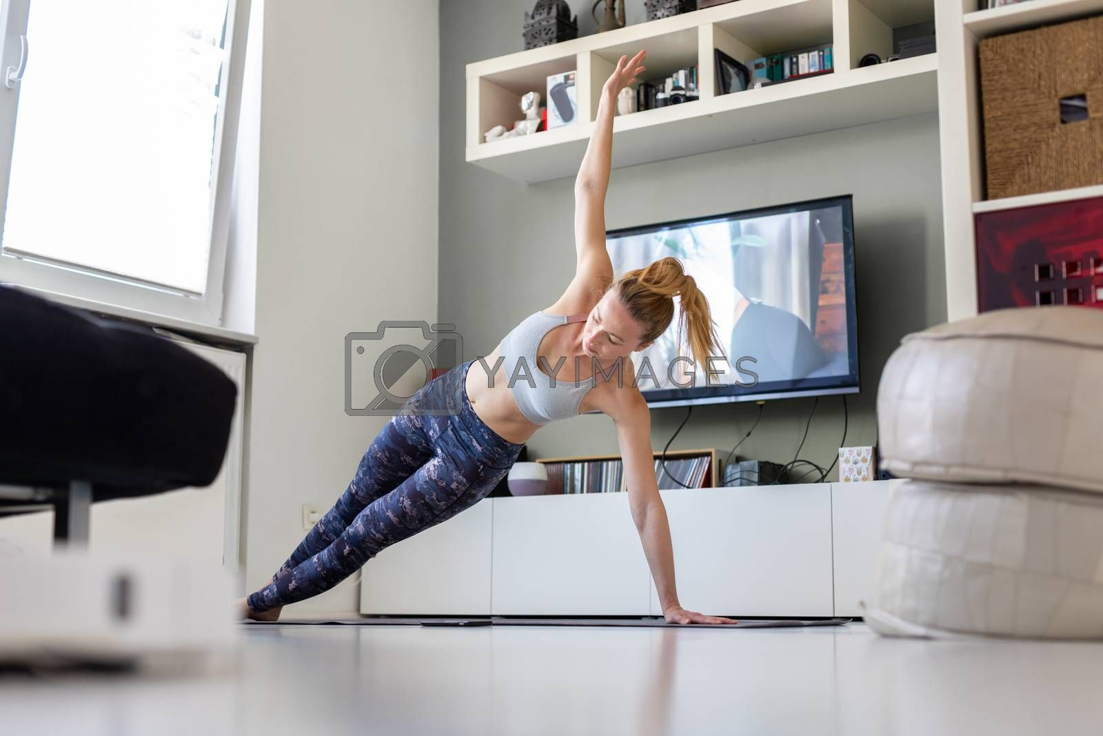 Attractive sporty woman working out at home, doing pilates exercise in front of television in her living room. Social distancing. Stay healthy and stay at home during corona virus pandemic.