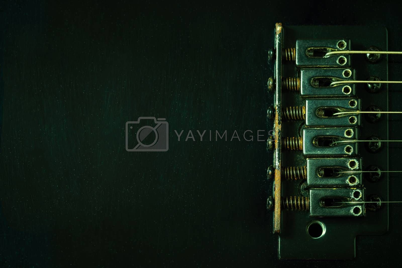 A closeup rust bridge serves to fasten or tighten the string. Black vintage electric guitar in dark. Top view and copy space. Concept of good memory About retro musical instruments and rock music.