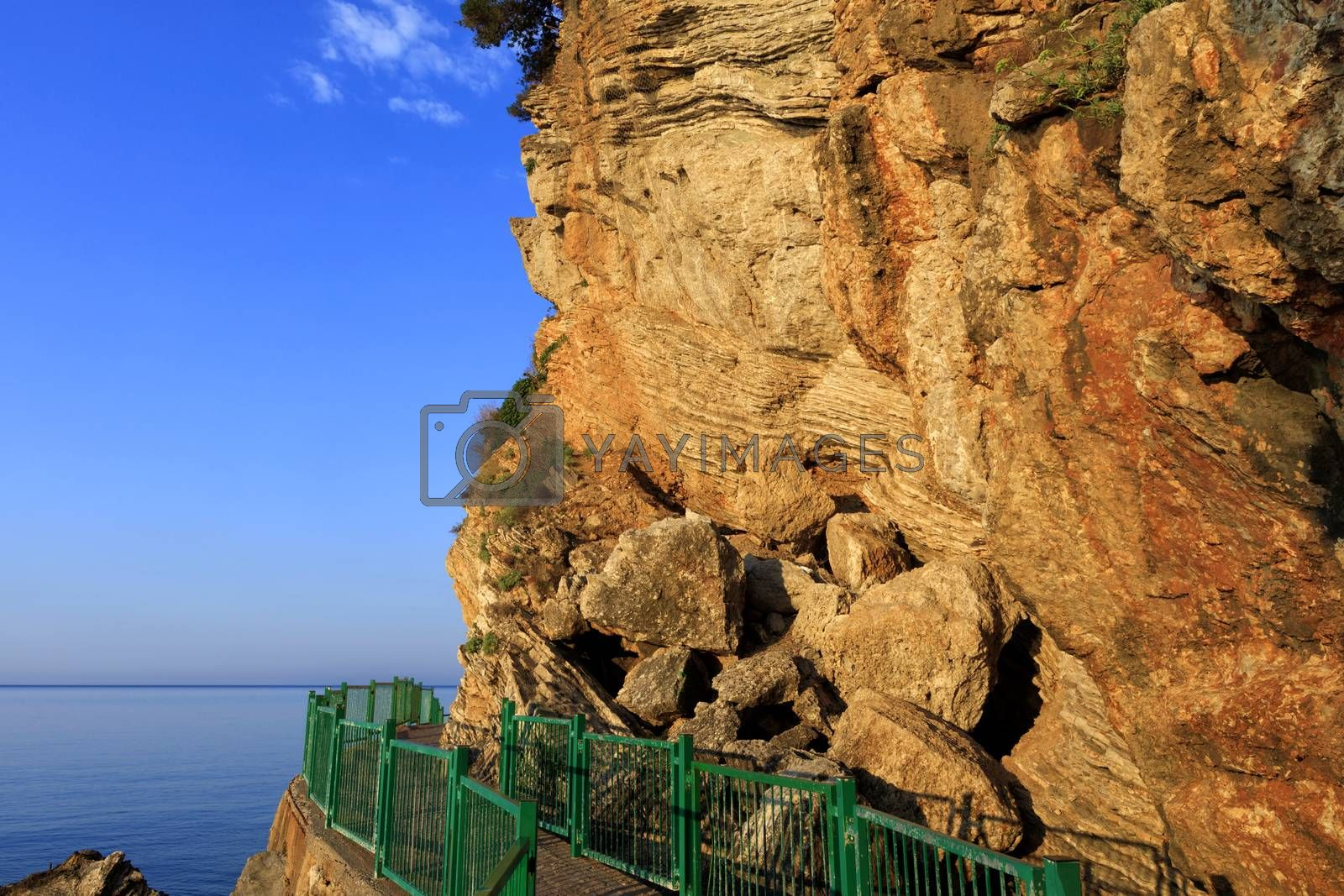 Beautiful and peaceful view of the fresh sea morning under the golden sunshine on a rocky mountain with huge stone boulders.