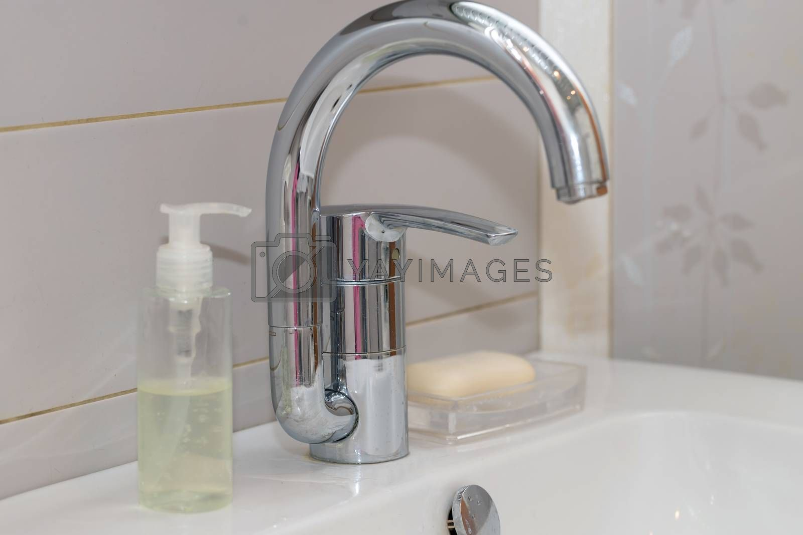 Modern hand wash basin. Solid tabletop surface and gray tile wall. Dispensable soap next to water tap on bathroom sink