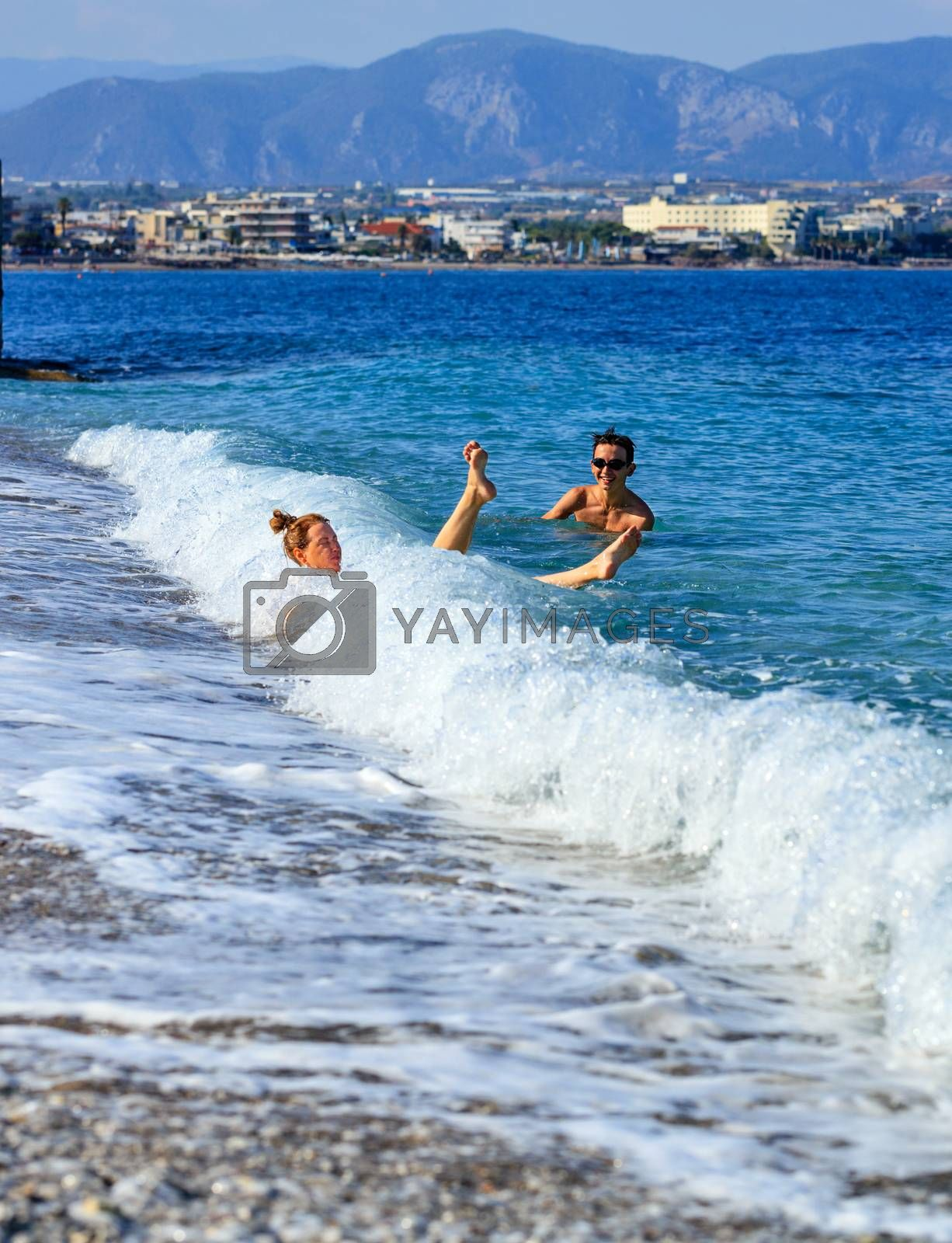 Mother and son swim merrily and relaxation at the sea surf, a beautiful sea wave with transparent and white foam on a pebble beach knocks down a young lady, image with copy space.