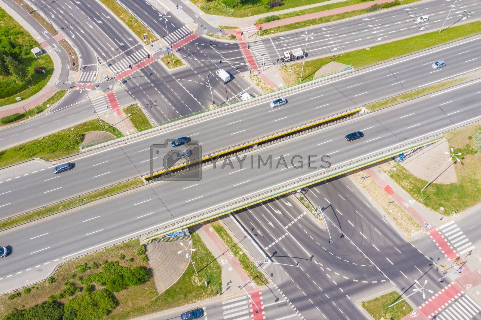 Aerial view of a freeway intersection. Clip. Highway and overpass with cars and trucks, interchange, two-level road junction in the big city. Top view