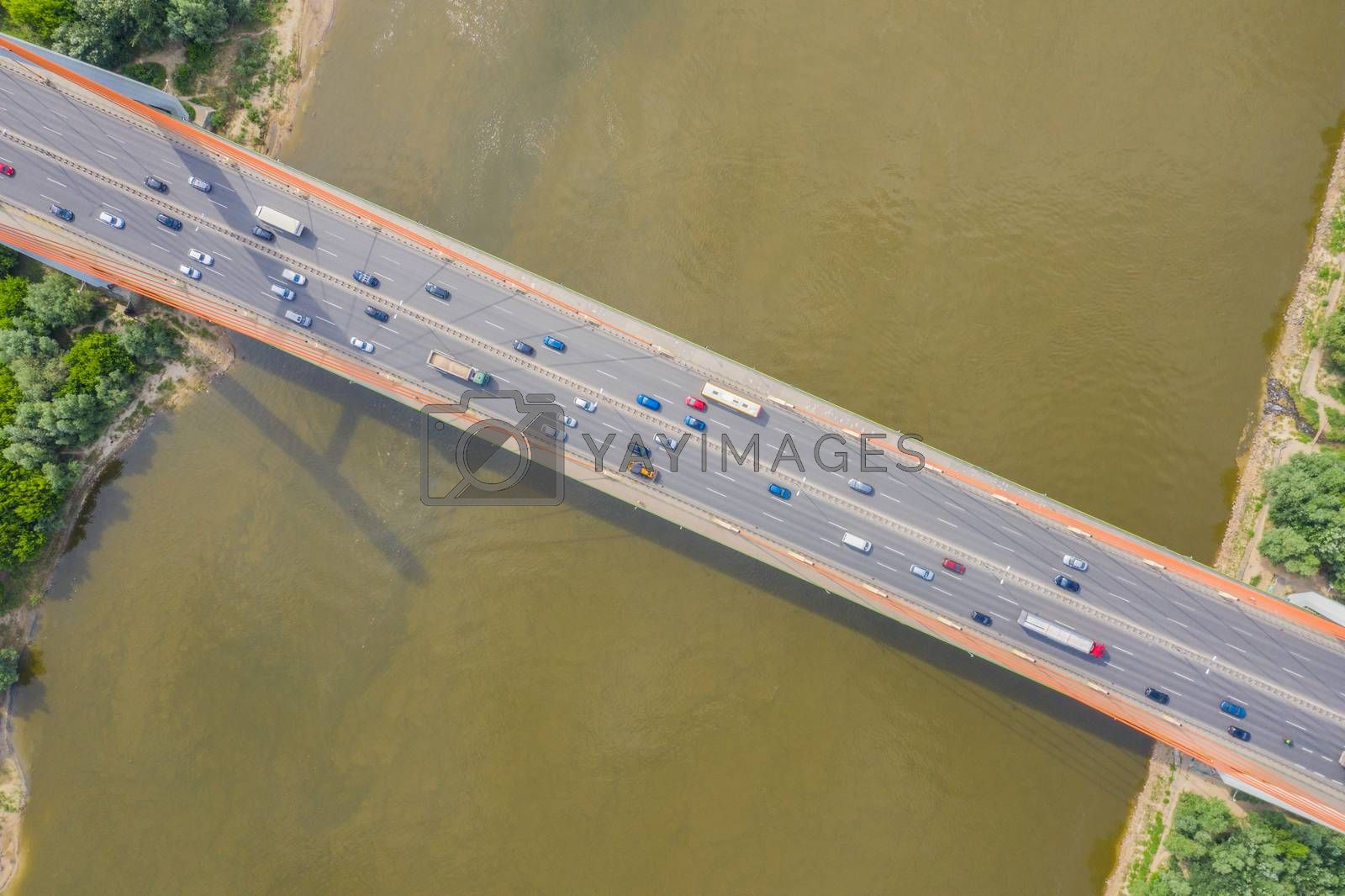 City car moving at highway bridge on background smooth river surface drone view. Aerial view