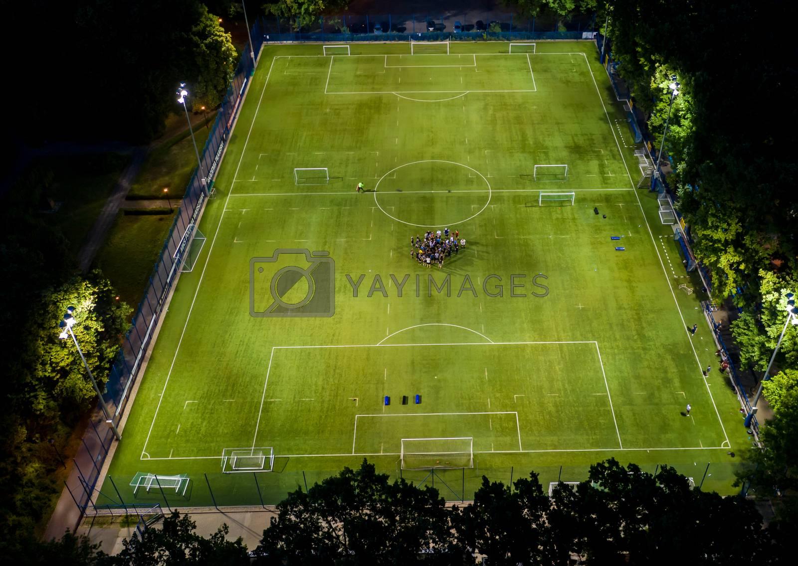 Aerial view on football stadium illuminated by jupiter on evening.