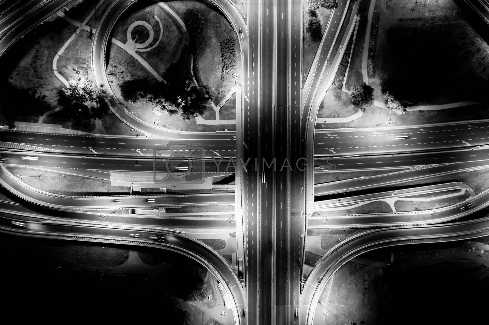 Aerial View Above of Busy Highway Road Junctions at Night. The Intersecting Freeway Road Overpass. Black and White