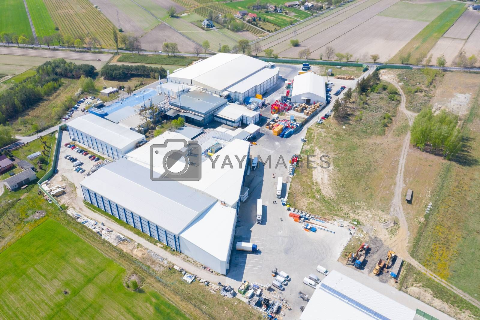 Aerial view of goods warehouse. Logistics center in industrial city zone from above. Aerial view of trucks loading at logistic center