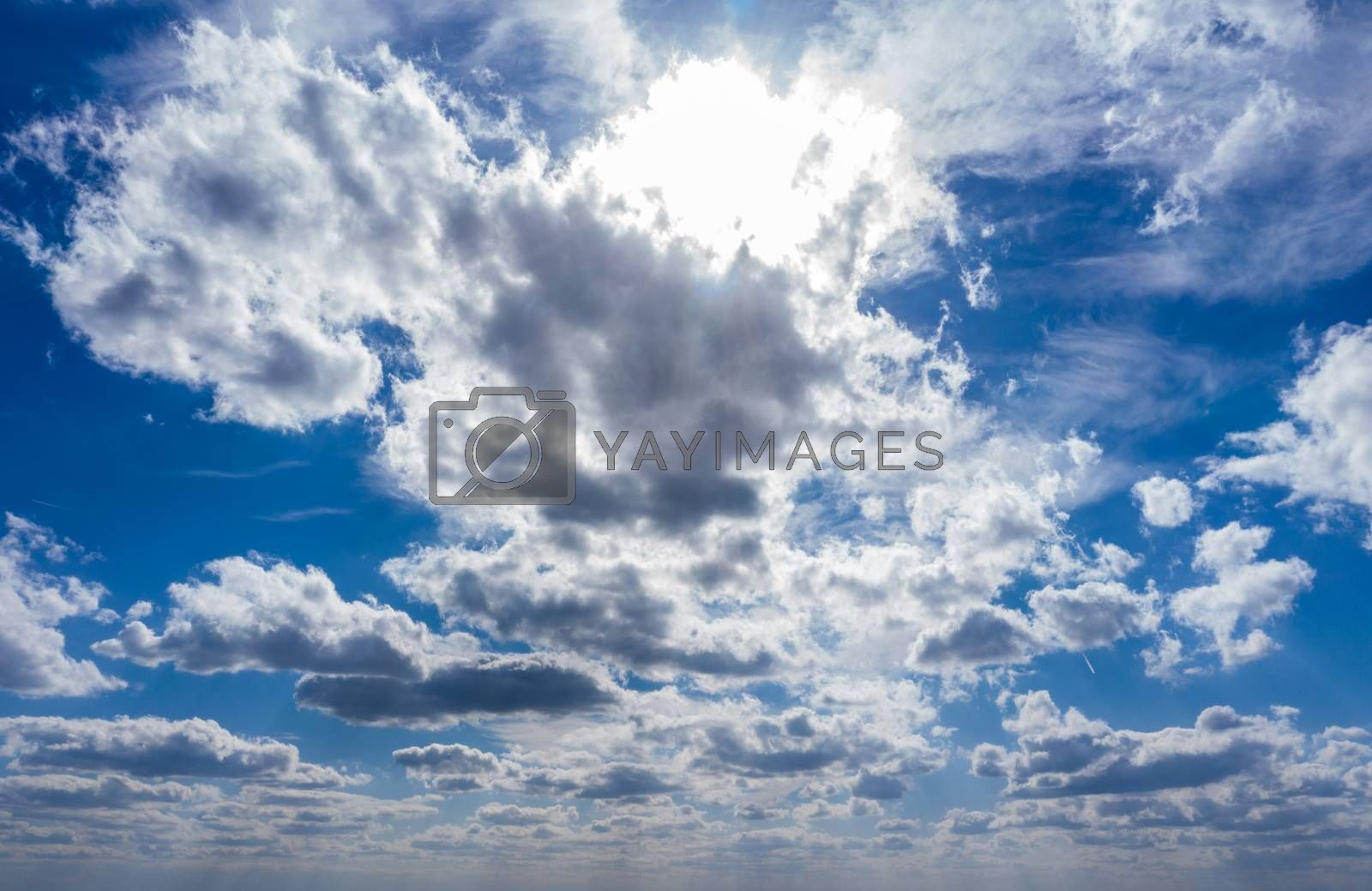 The sun with bright rays in the blue sky with white light clouds