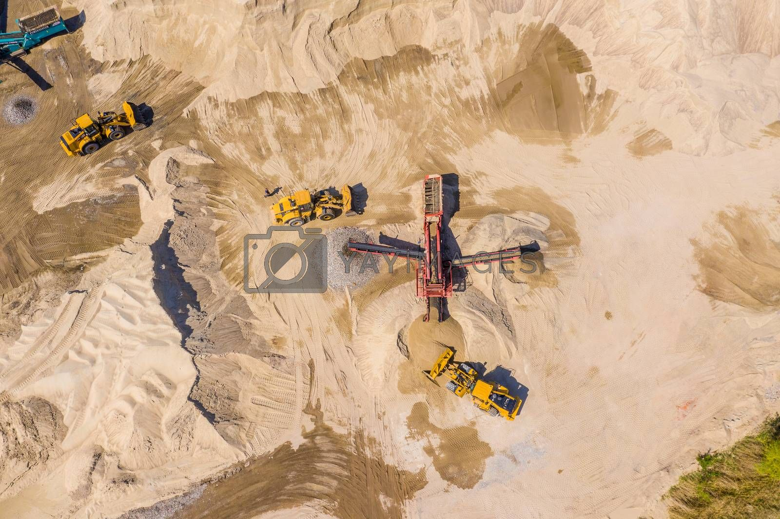 Aerial view of bulldozer pouring sand into truck