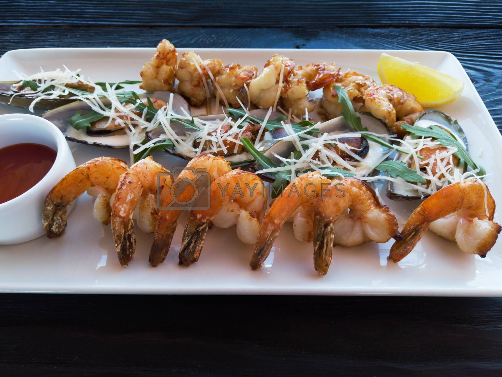 Fried shrimps and mussels with sauce and lemon on plate