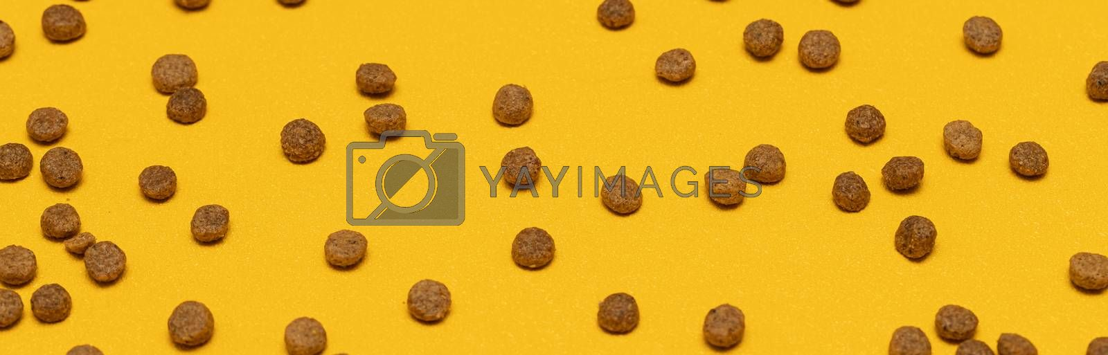 Balls of cat food on a yellow background. Background of pet food.