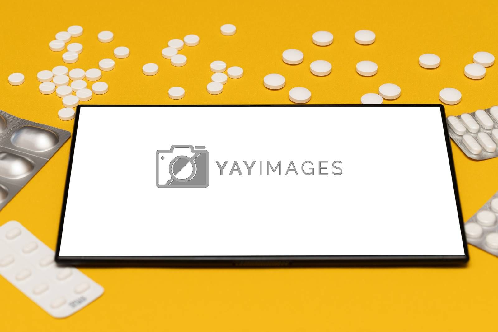 flat lay order, purchase of medicines, tablets online via the app on a tablet, on a yellow background with a copy of the space. E-health, e-medicine, payment for services concept. Online purchasing
