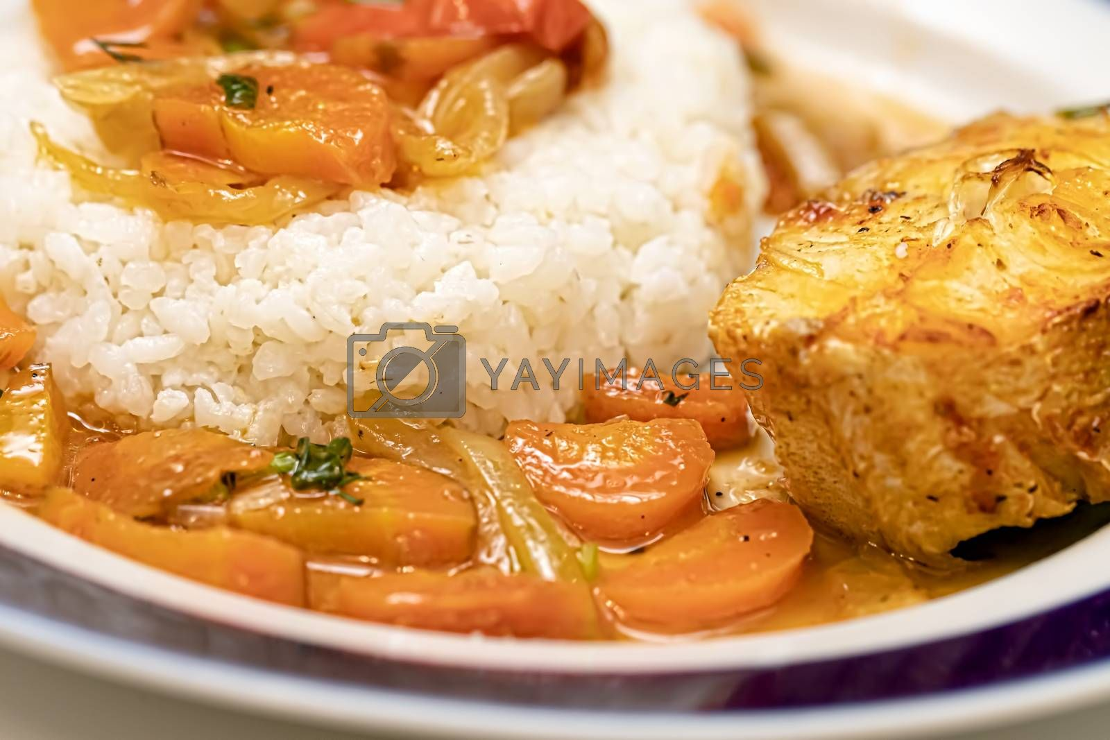 Fish is baked in the oven with onions and carrot slices and served with a side dish of rice. Flexitarian Diet Concept
