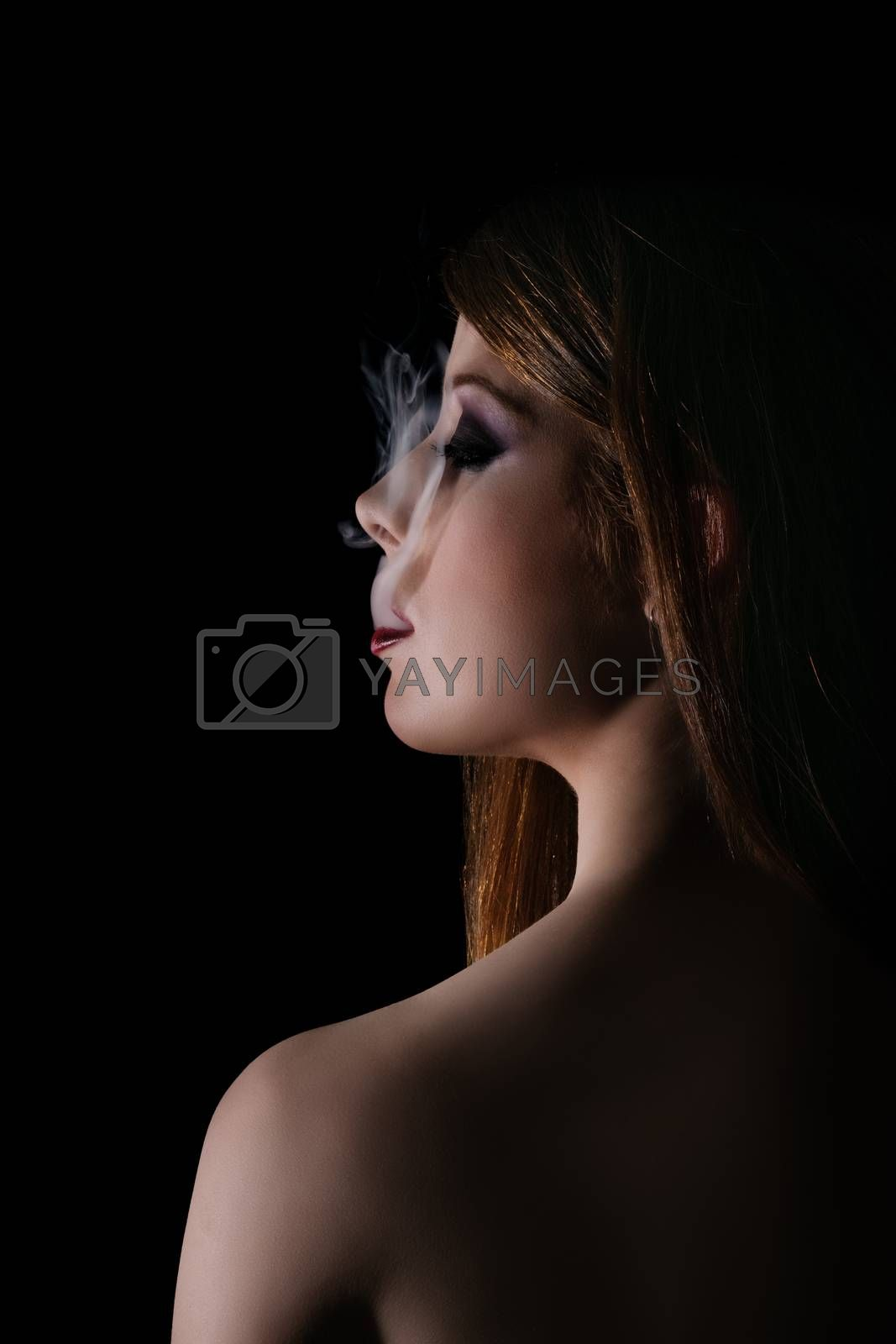 Low key profile shot of a gorgeous young woman with smokey eye makeup and red lipstick, smoke coming out of her mouth, isolated on black background. Smoking concept. Night, beauty, mystery, gothic style, fashion concept.