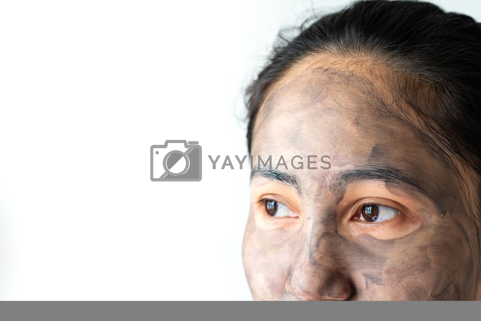 asia woman applied charcoal mask on her bare face