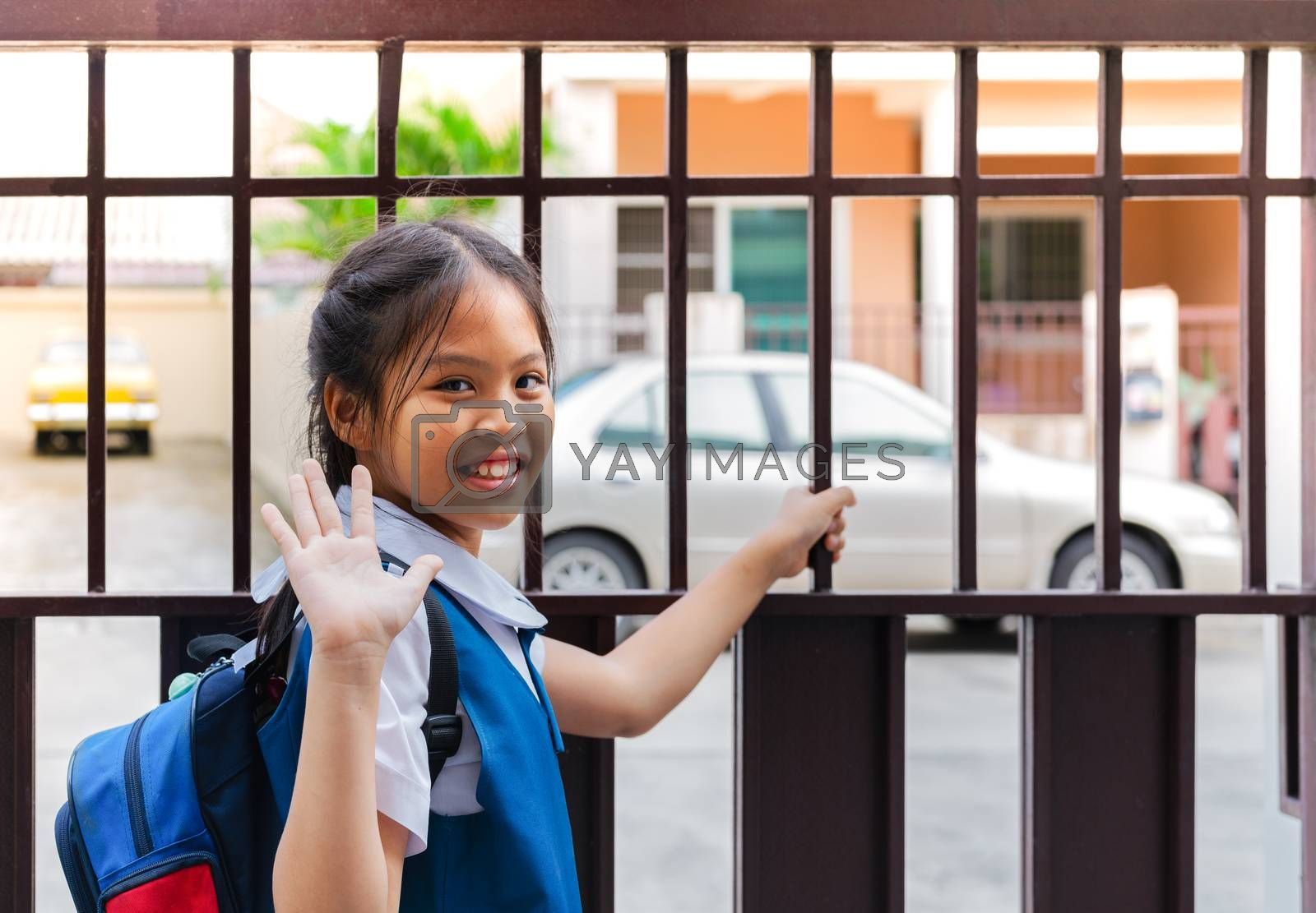 Little asian girl in uniform say good bye before leaving to school in the morning with blue back pack