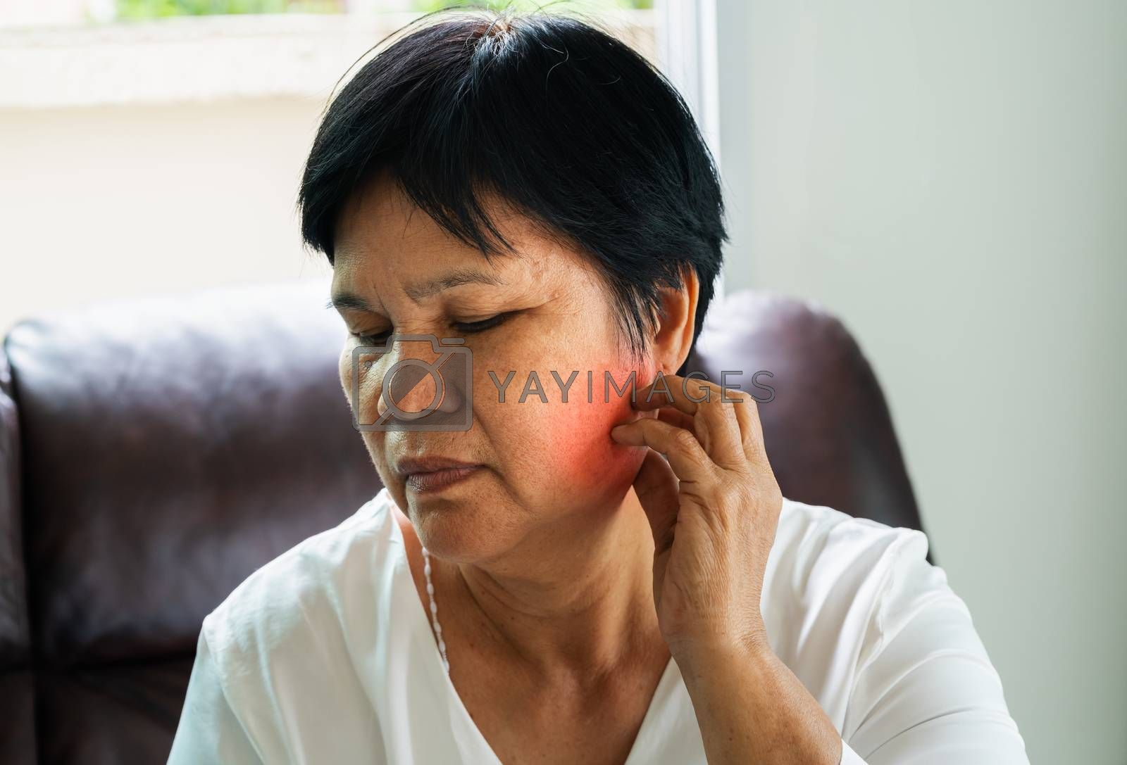 portrait of old woman have toothache at home