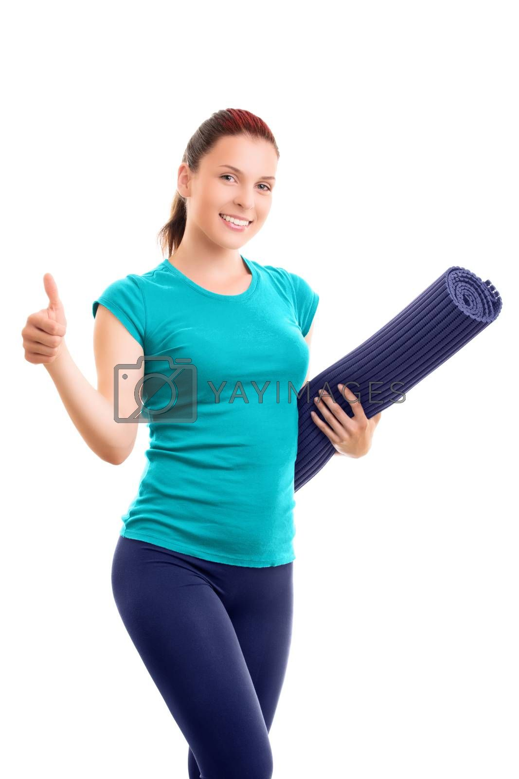 Beautiful smiling young girl in sportswear holding a yoga mat giving thumbs up, isolated on white background. Healthy lifestyle concept. Fitness and yoga concept.