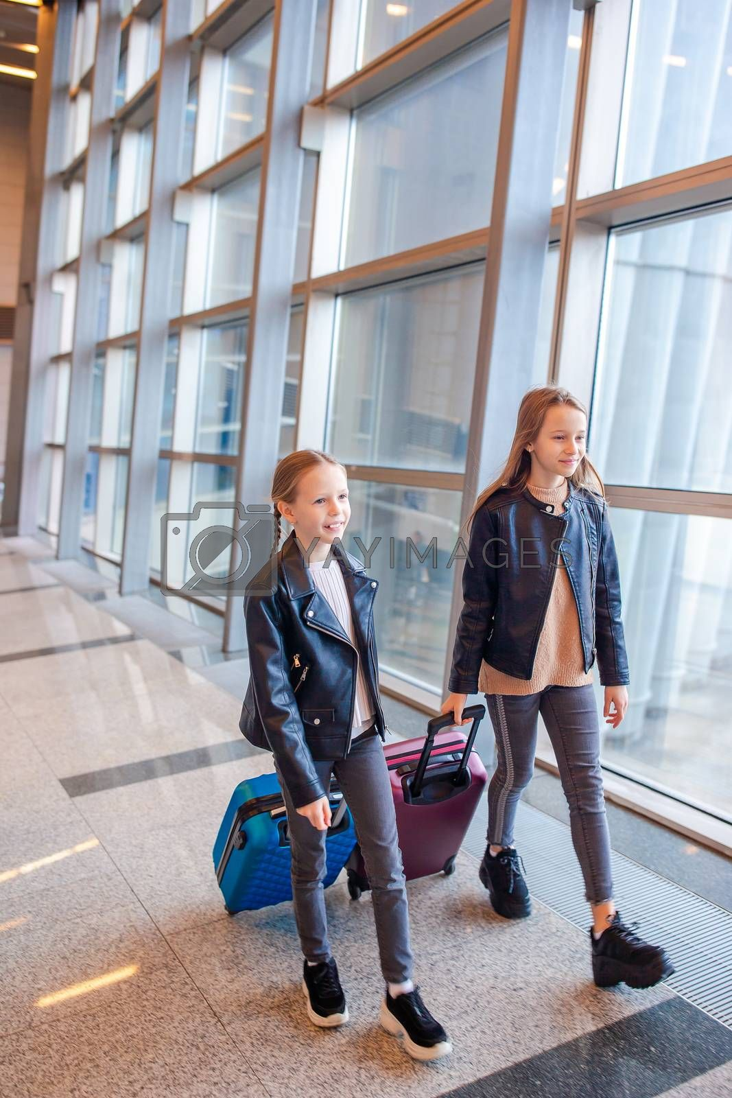 Little adorable kids in international airport waiting for boarding indoors