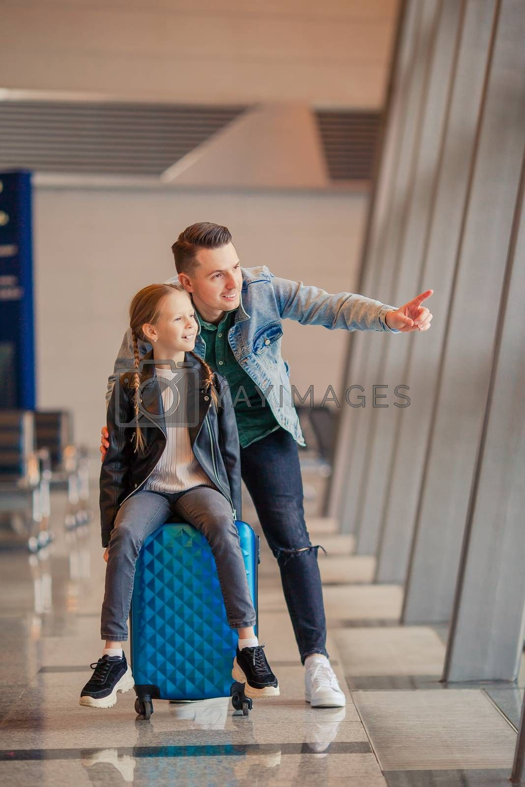 Young father and little daughter looking out the window at airport terminal waiting for boarding