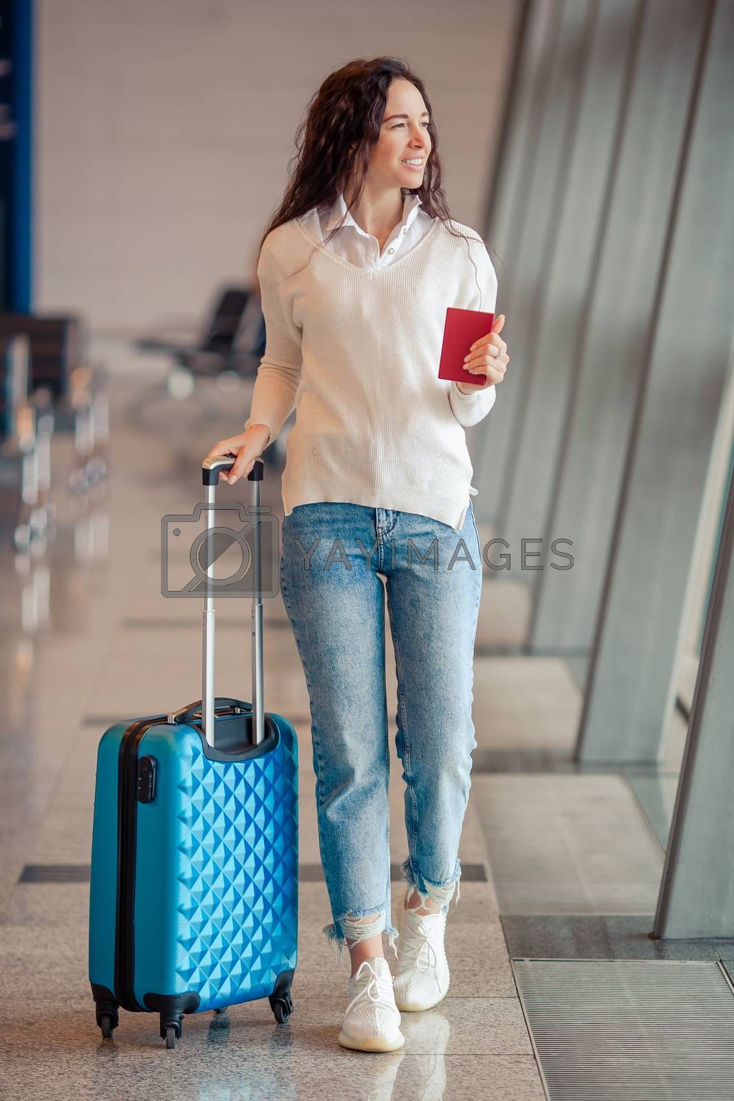 Young woman in international airport walking with her luggage. Airline passenger in an airport lounge waiting for flight aircraft