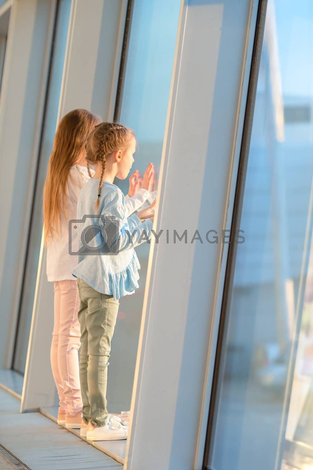 Little kids in airport waiting for boarding and looking at window on the planes