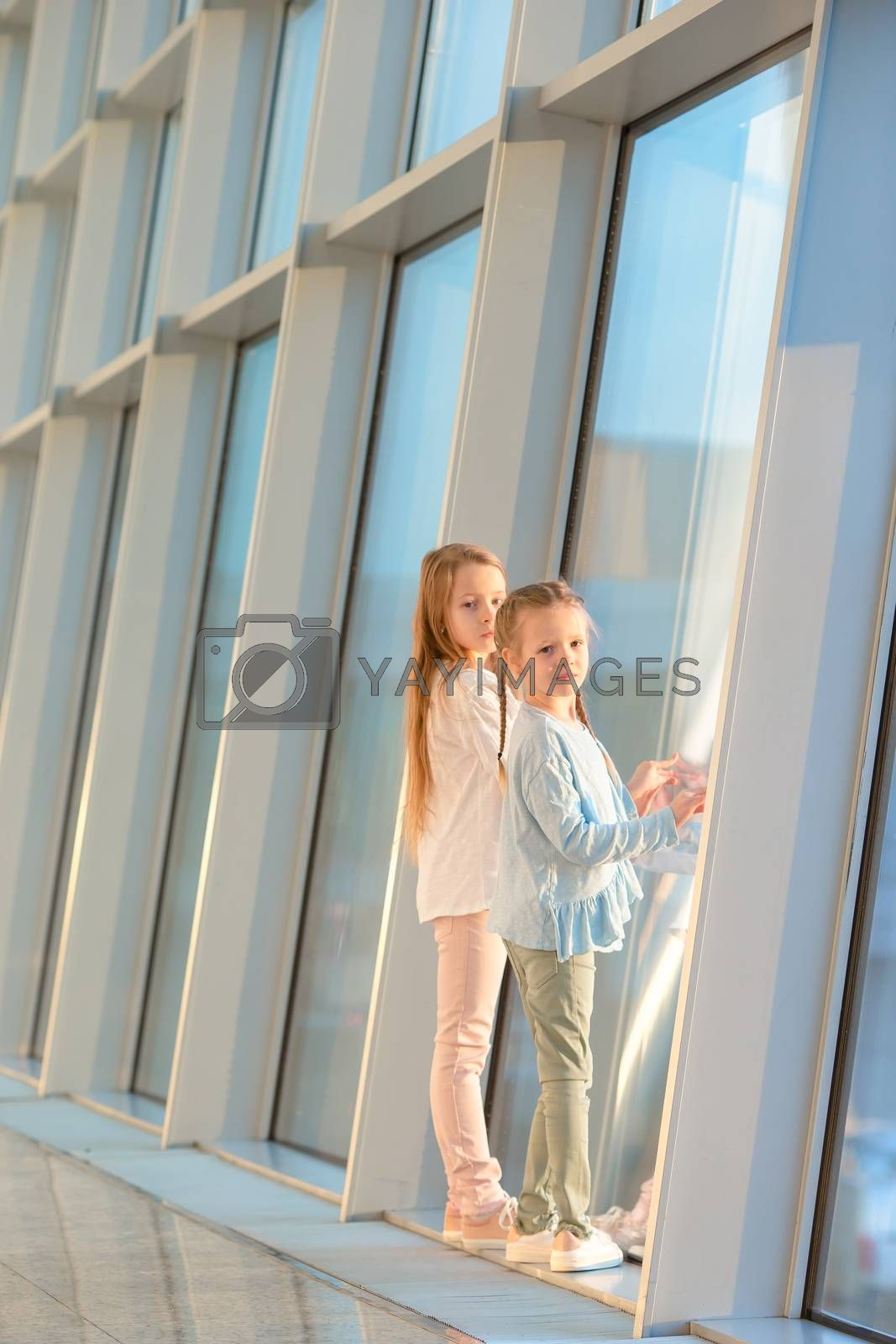 Girls in international airport waiting for boarding and looking at window on the aircrafts