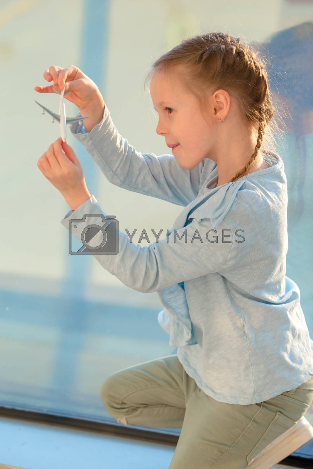 Little girl in airport near big window waiting for boarding