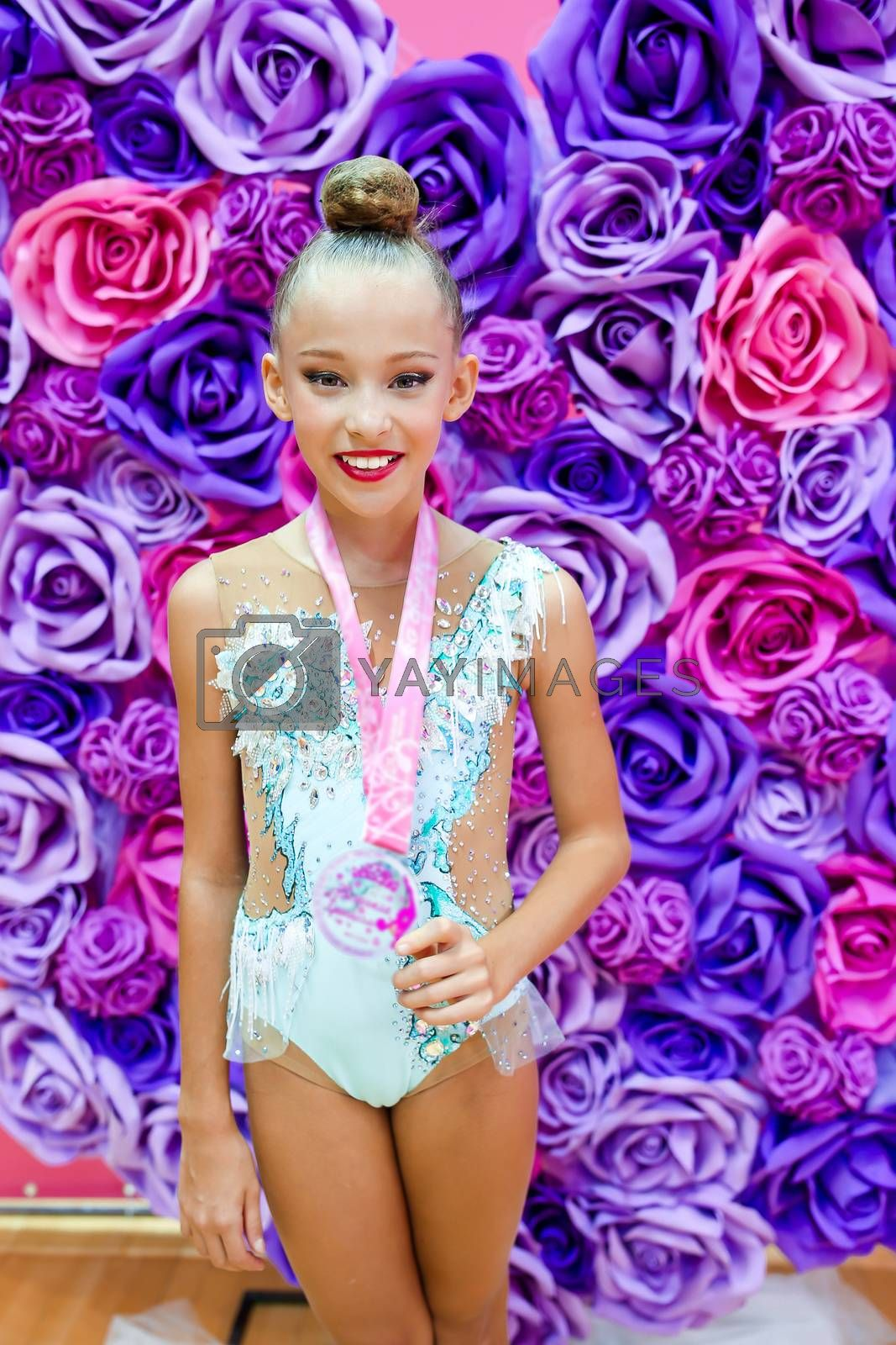 Little gymnast with her sports awards on the carpet