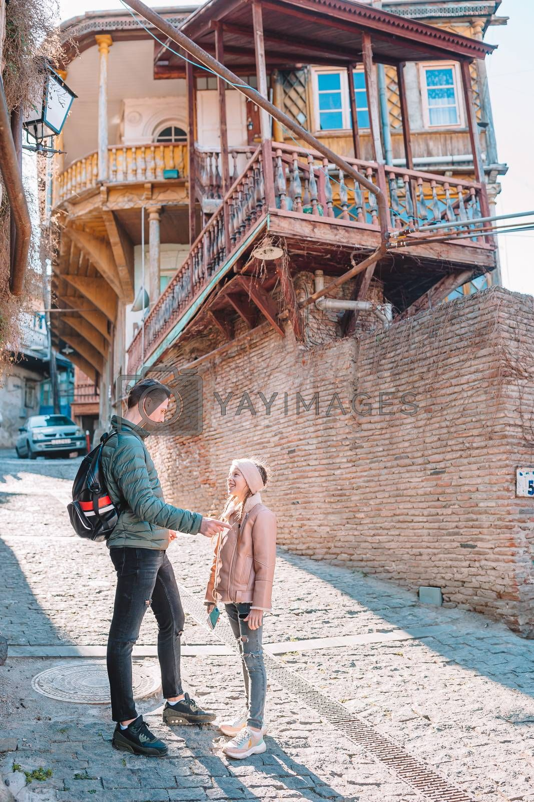 Family walking in old quarter in Tbilisi city in sunny day, Georgia country
