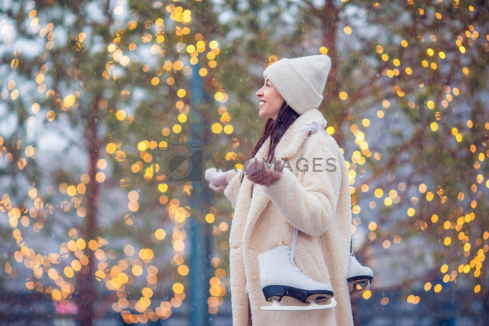 Happy young woman ready to skate on ice rink outdoors