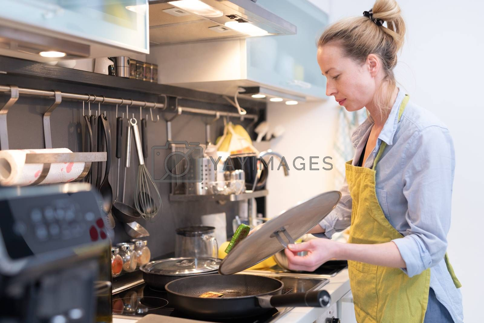 Stay at home housewife woman cooking in kitchen, stir frying dish in a saucepan, preparing food for family dinner. Blonde caucasian model in her 30is, real cooking not looking in camera.