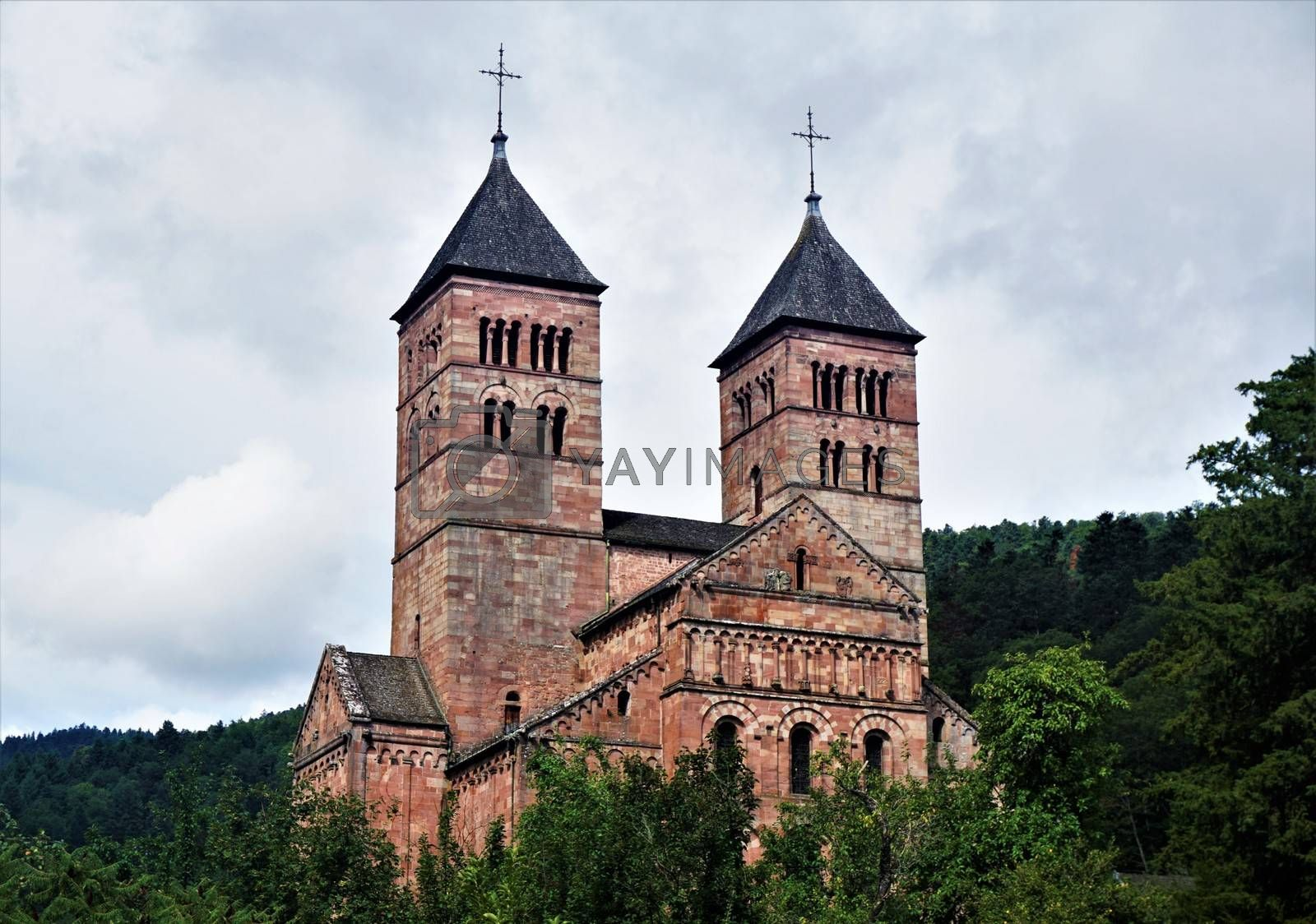 Steeples of Murbach Abbey looming out of the forest in the Vosges, France