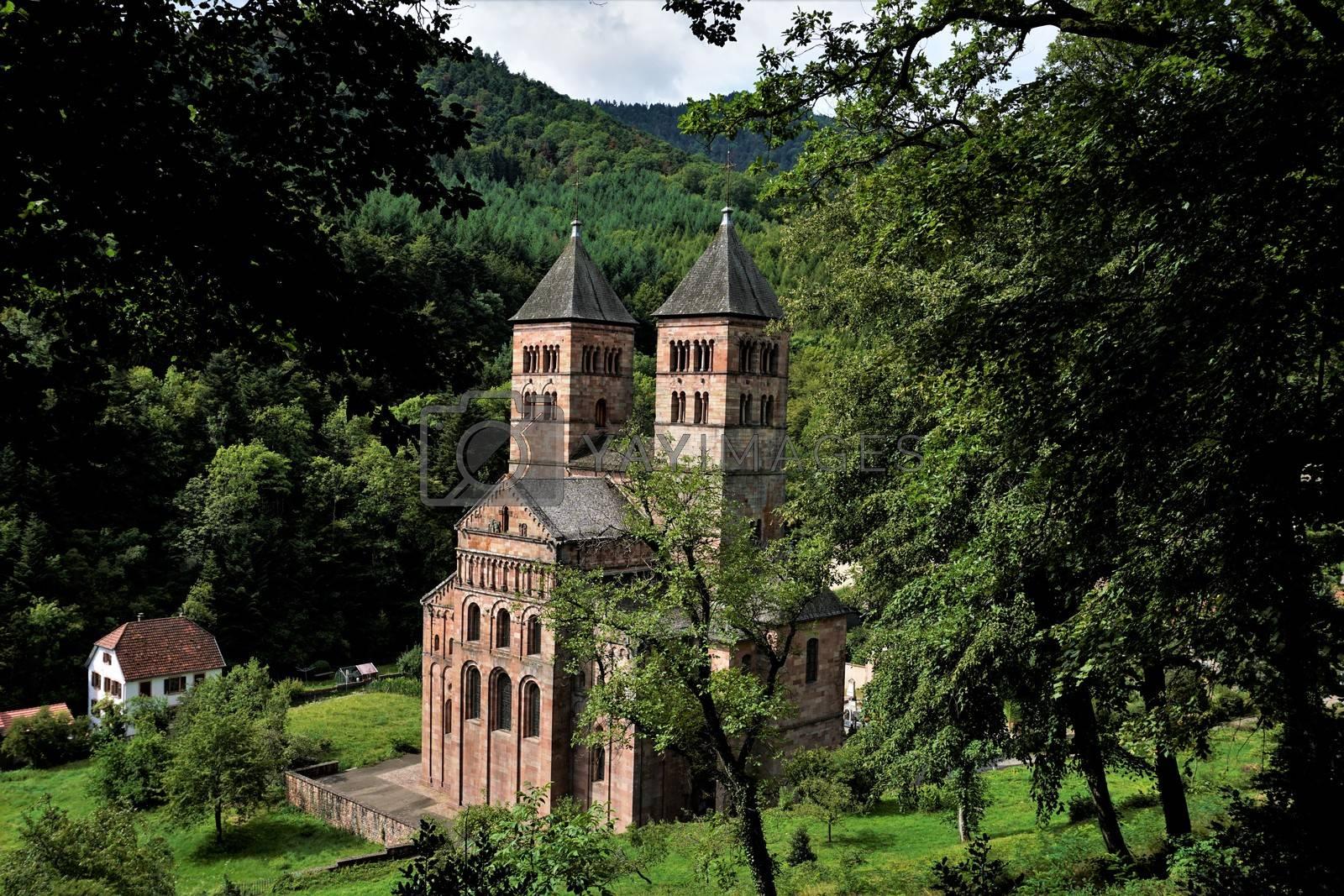Murbach Abbey hidden behind trees with town hall of Murbach, France