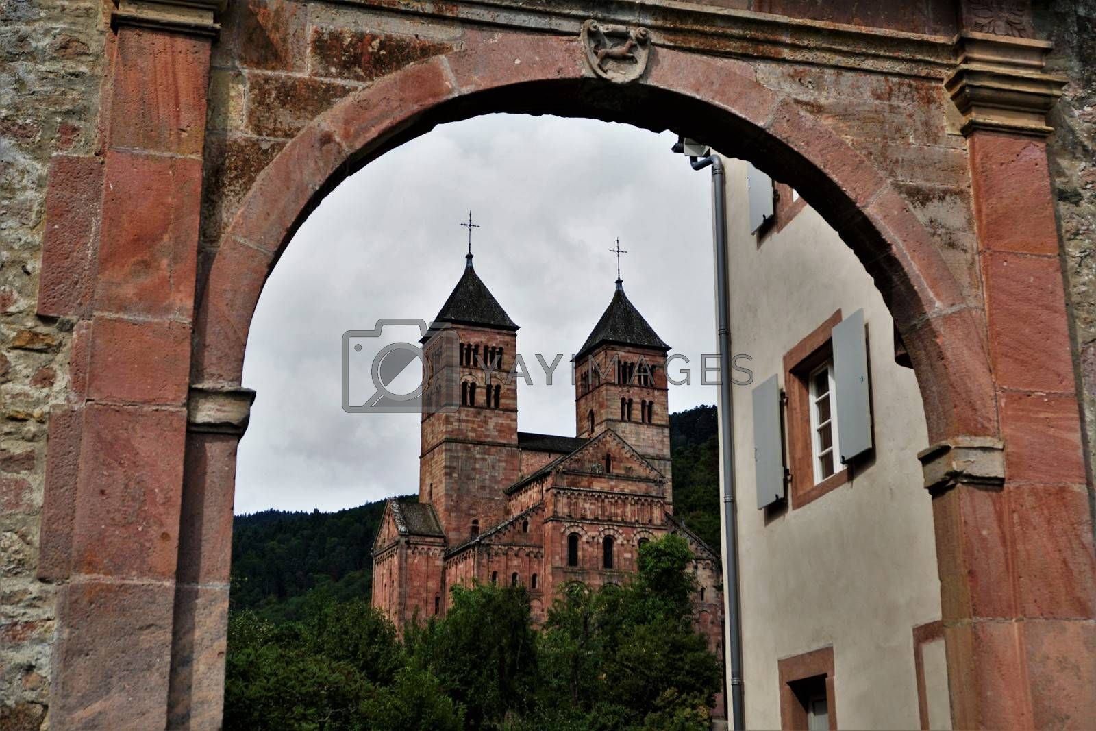 View to Murbach Abbey through a red stone arch