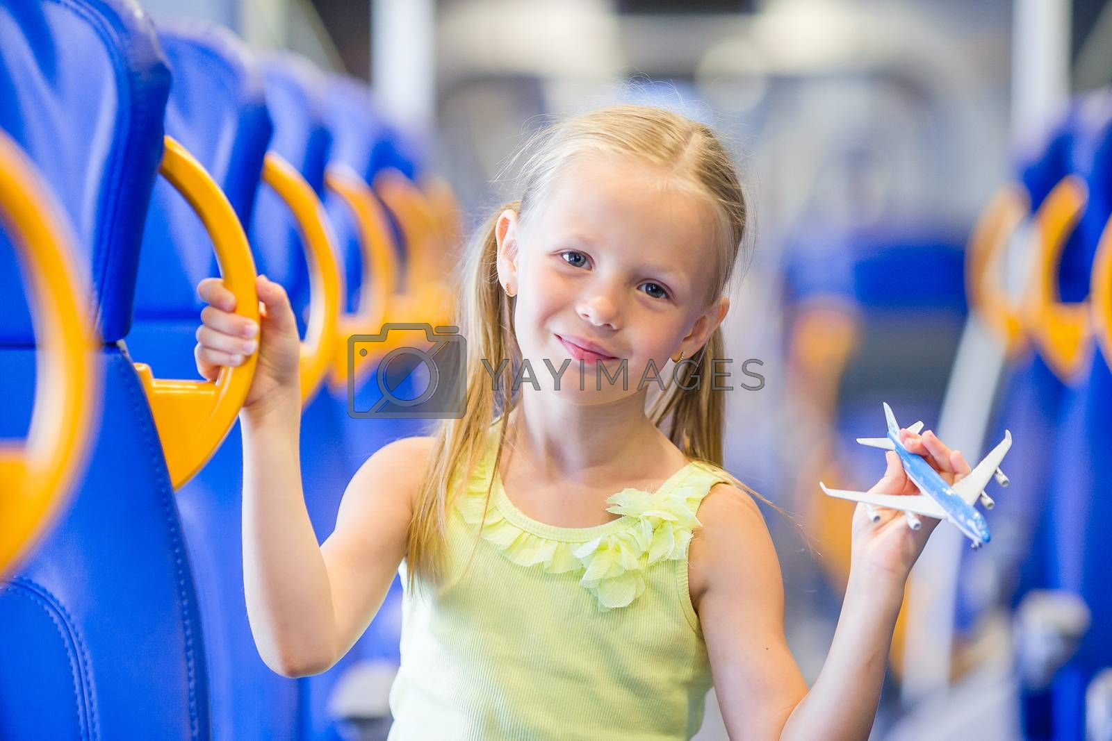 Adorable little girl traveling on train and having fun with airplane model in hands by travnikovstudio