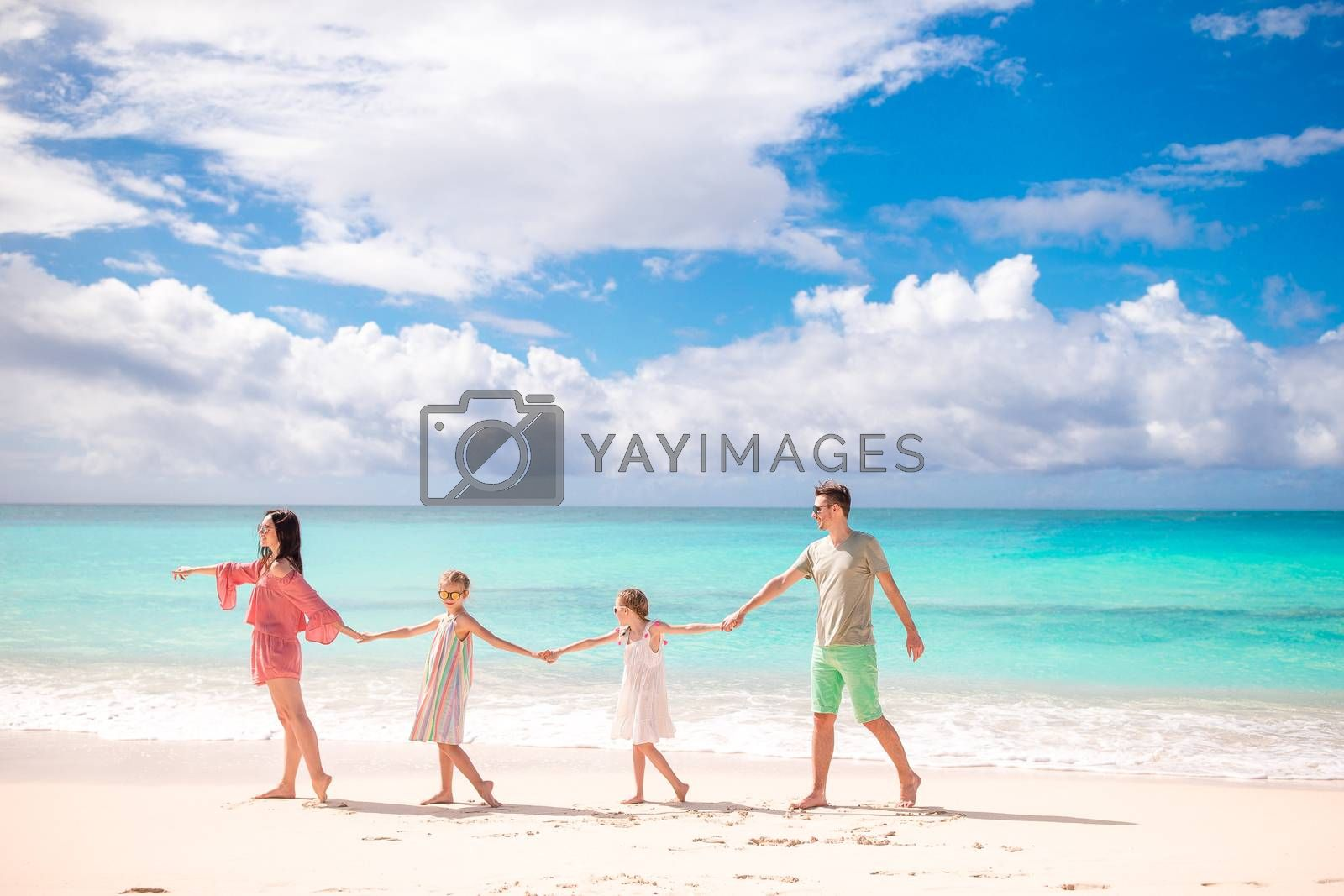 Happy beautiful family on white beach having fun