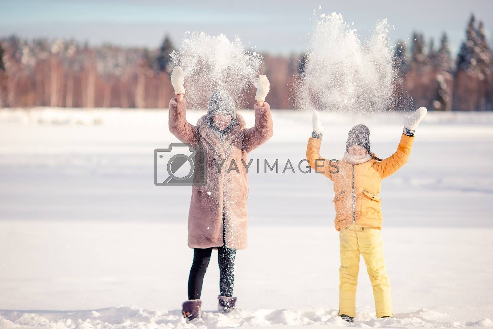 Happy family having fun outdoors in winter with snow